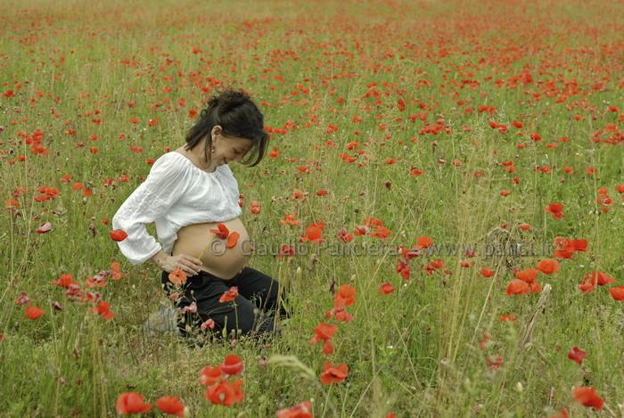 Donna incinta in un campo di fiori